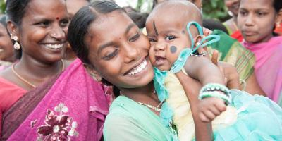 Annandhi holds a baby, smiling