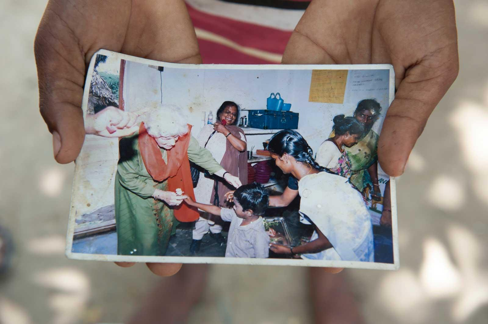 Hands holding old photo of Rosi and Balahandran