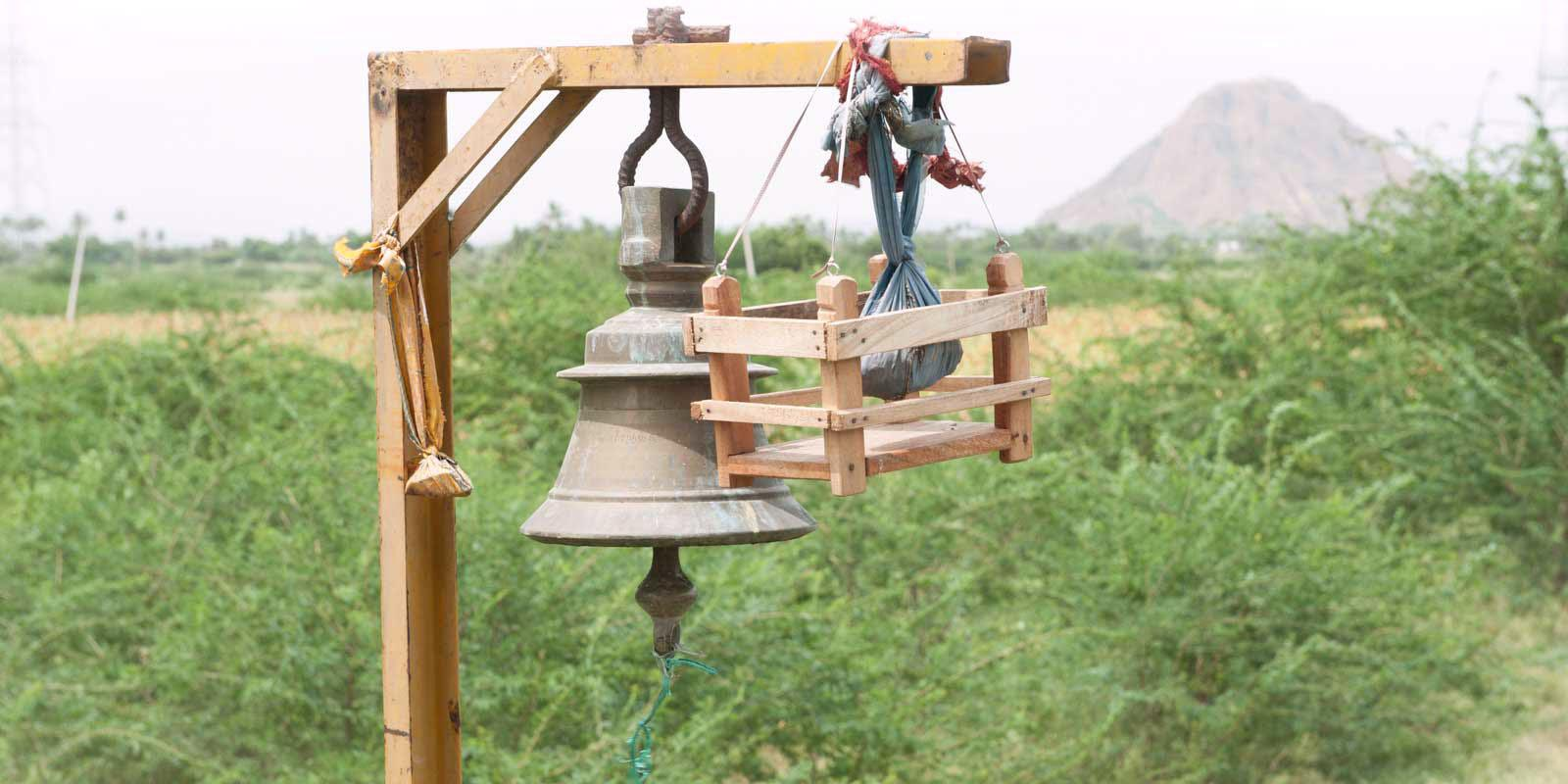 A temple bell with offerings tied to it.
