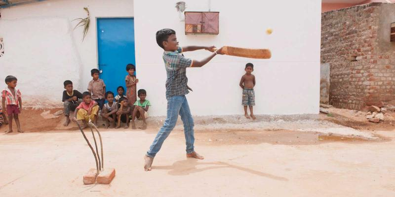 Boy hitting a cricket ball