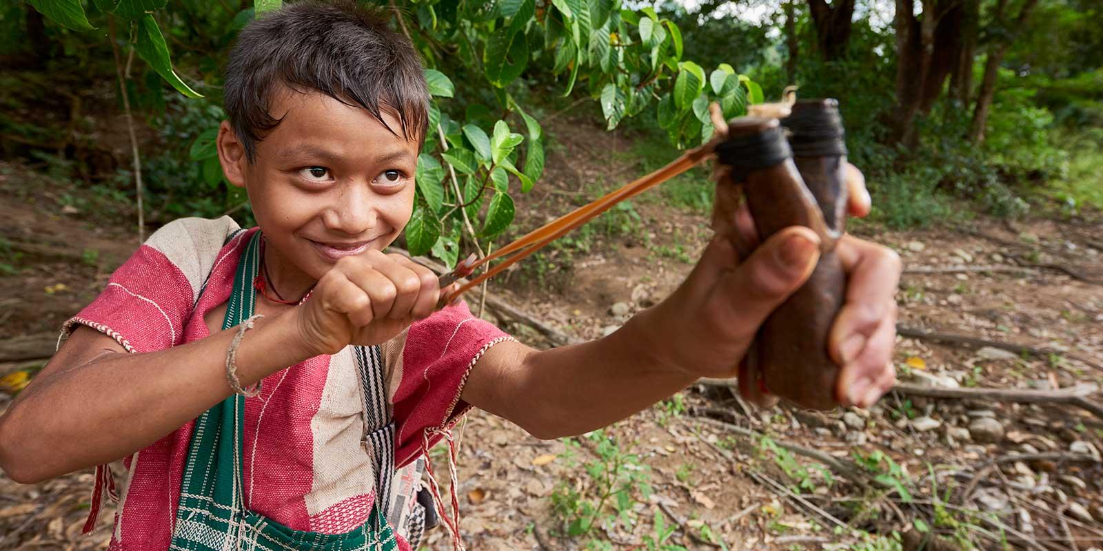 Boy with slingshot in rain forest