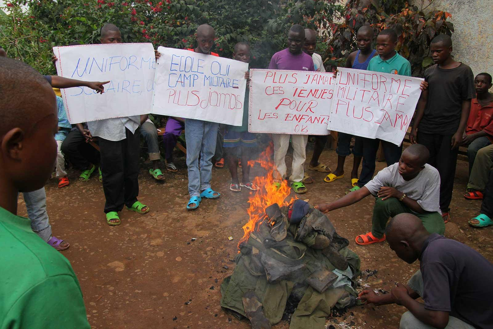 Former child soldiers burning their uniforms