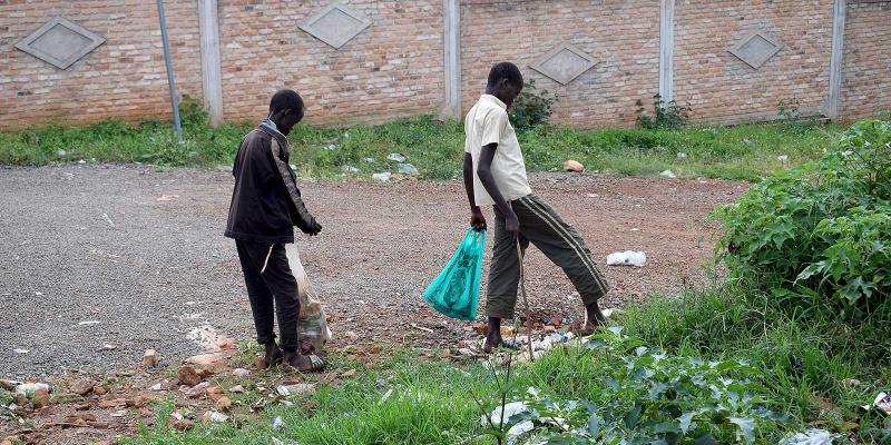 two boys collecting litter