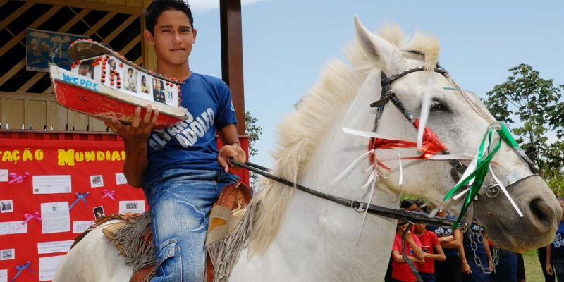 a boy with a ballot box on a horse