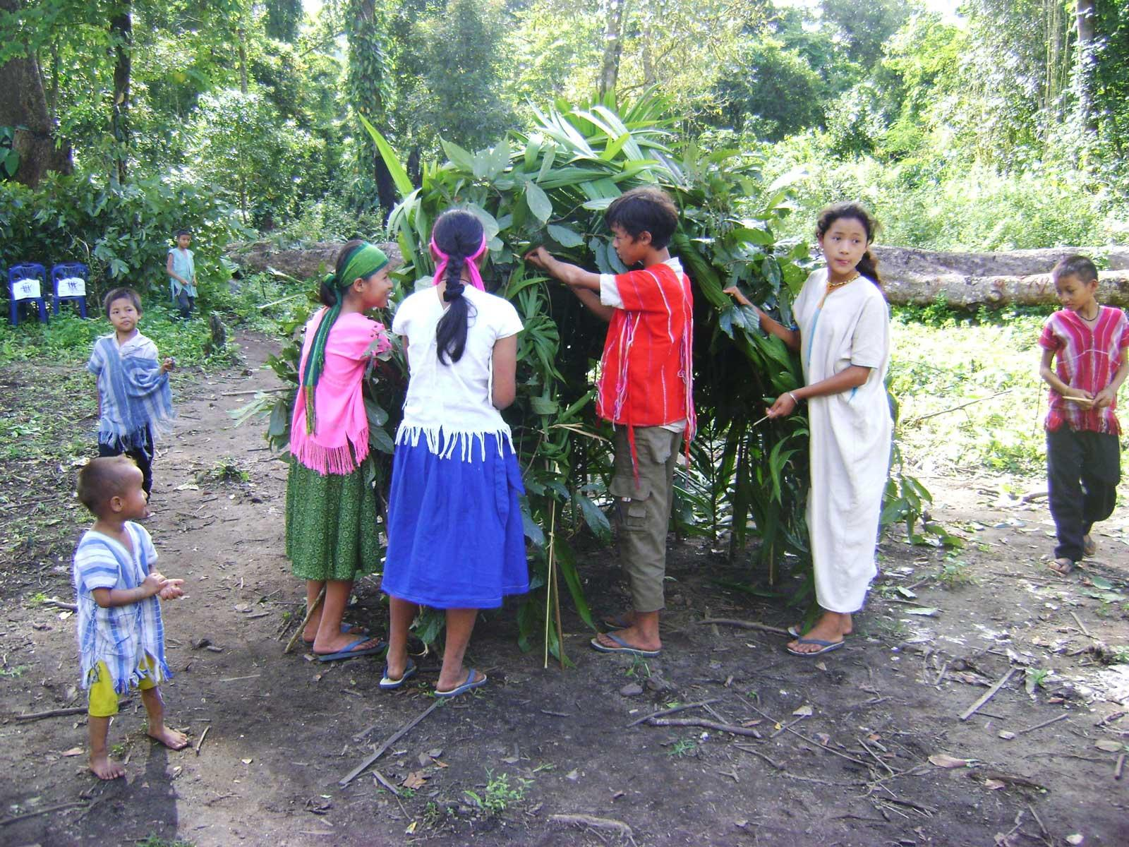 a group of children building a booth with plants