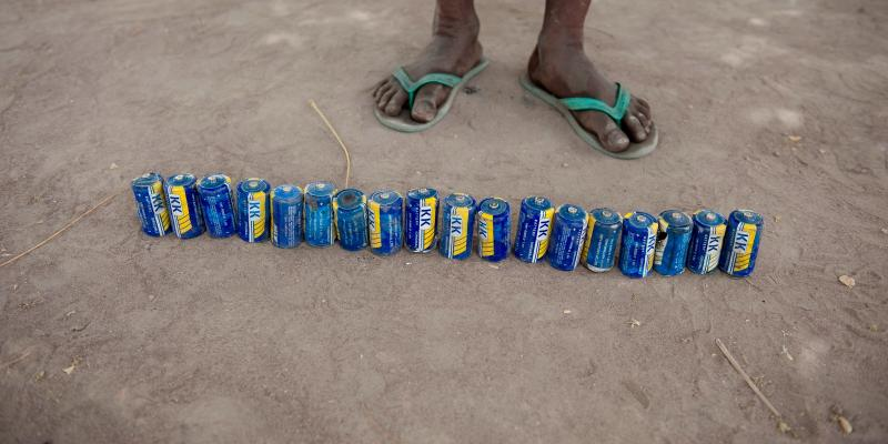 Line of cans in front of a pair of feet