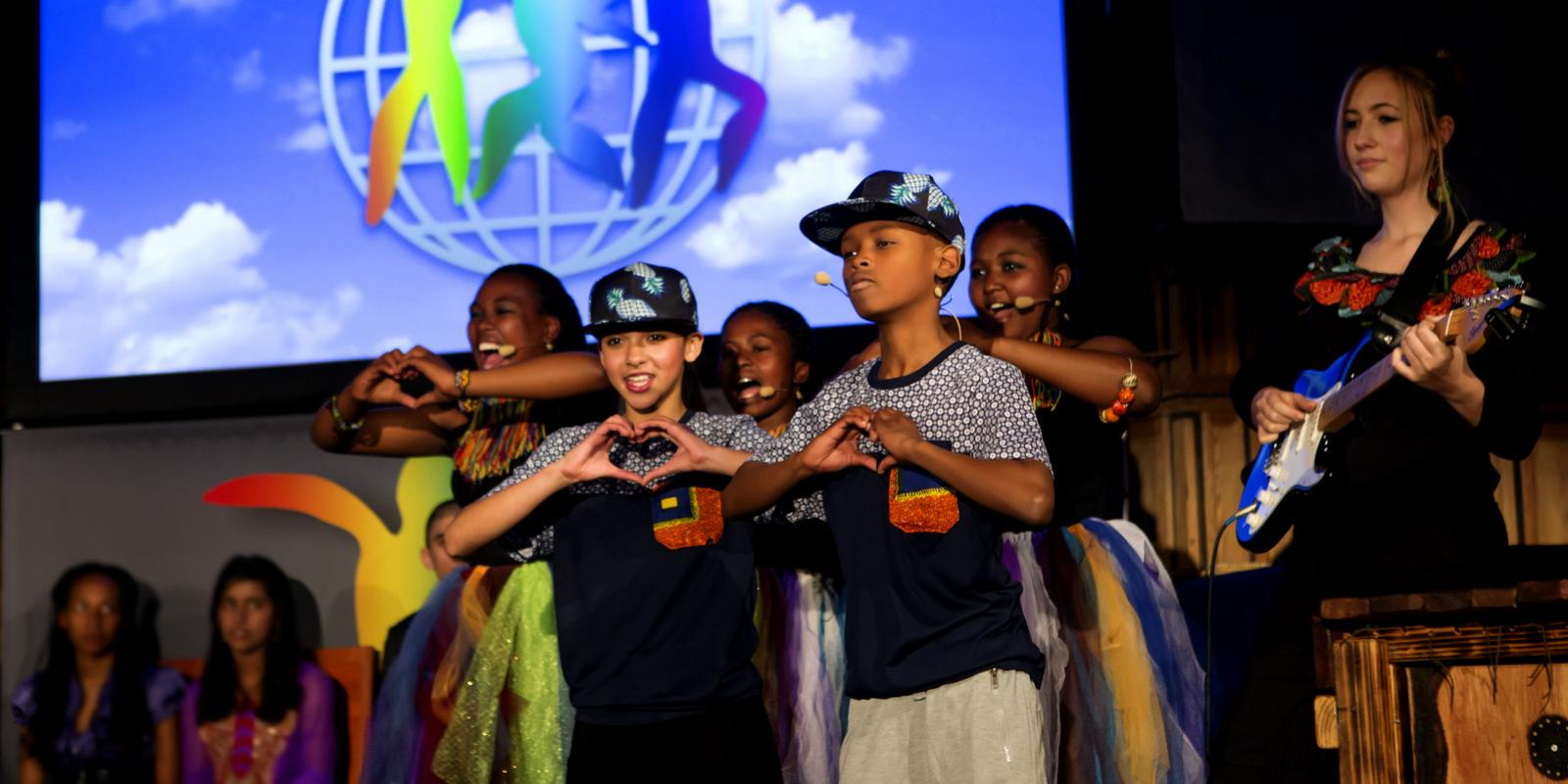 Children forming hearts with their hands while performing on stage.