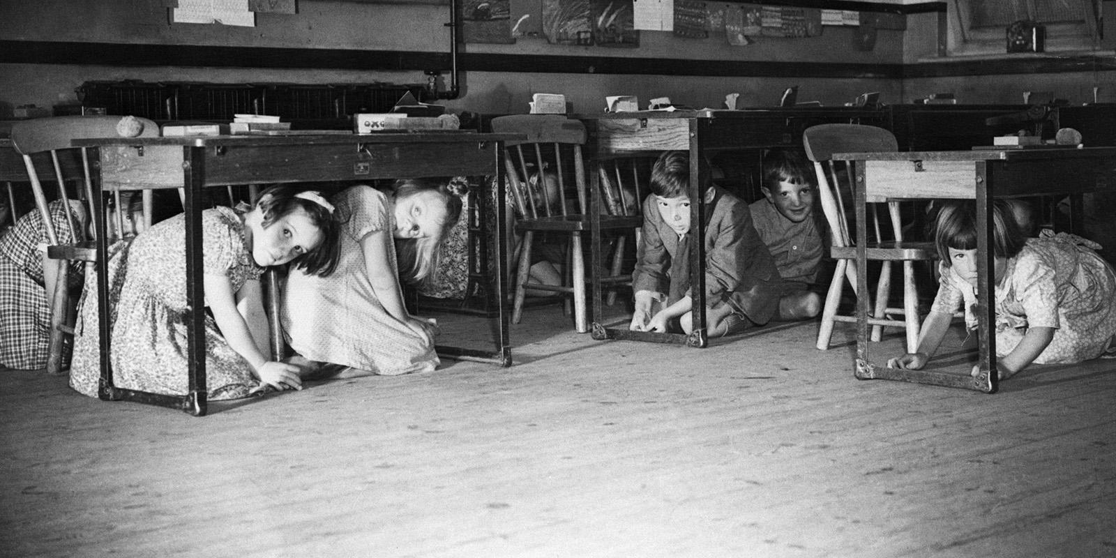 Children in classroom, hiding under tables