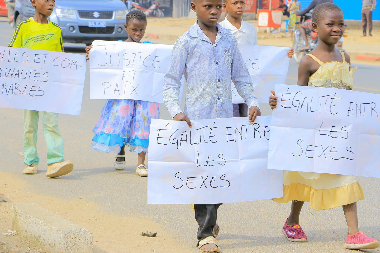 Kids walking with signs.