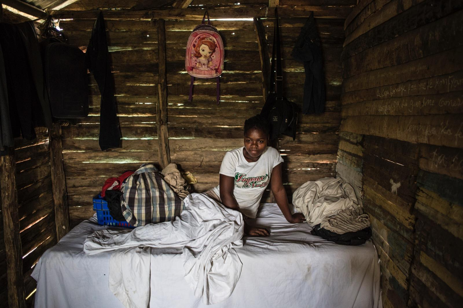 A girl in a bed inside a hut.