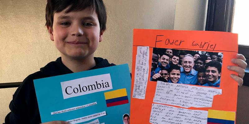 Boy showing his school project, posters about Colombia.