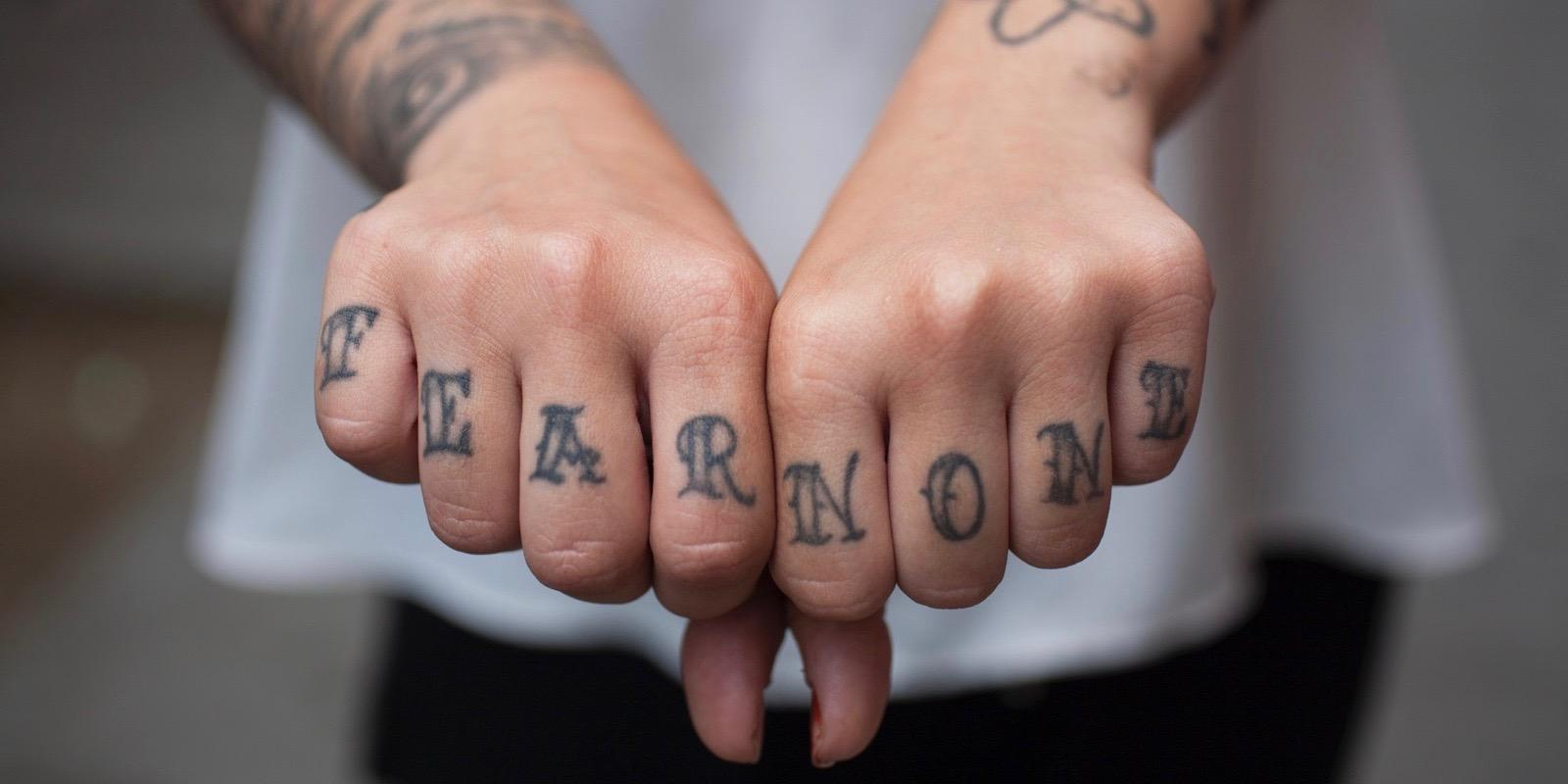 Girl holding out hands with tatoos