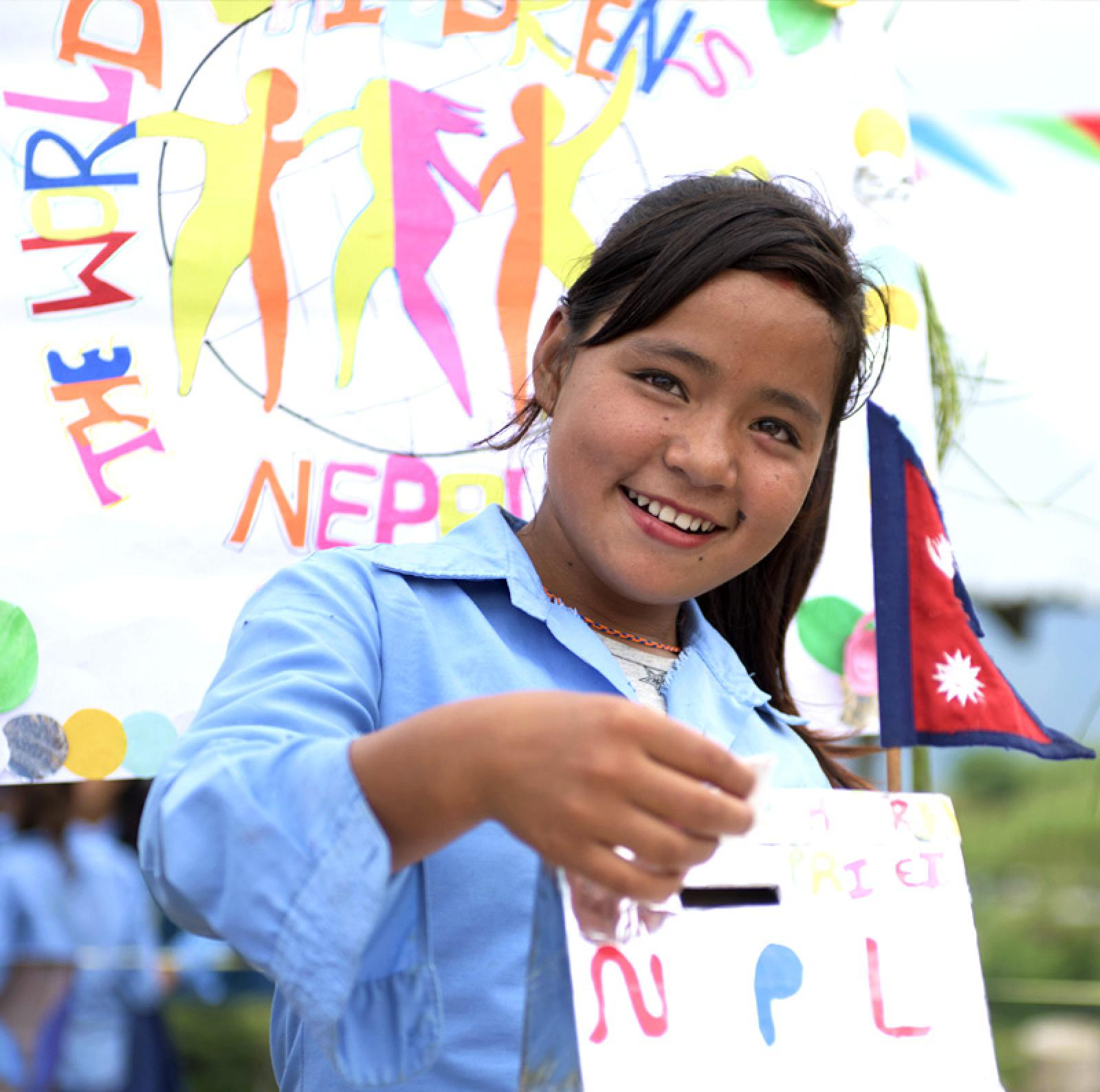 Nepali girls painting a sign