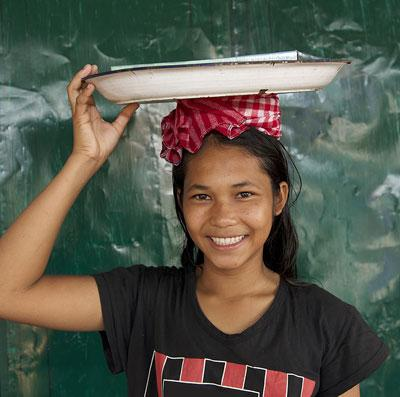 Girl in Cambodia with tray on head