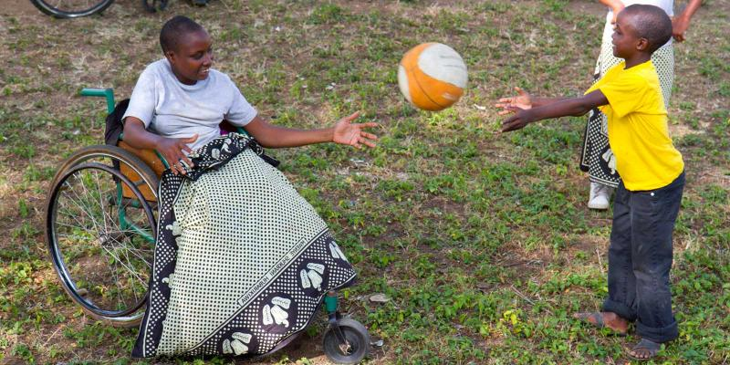 Girl in wheelchair playing ball with young boy