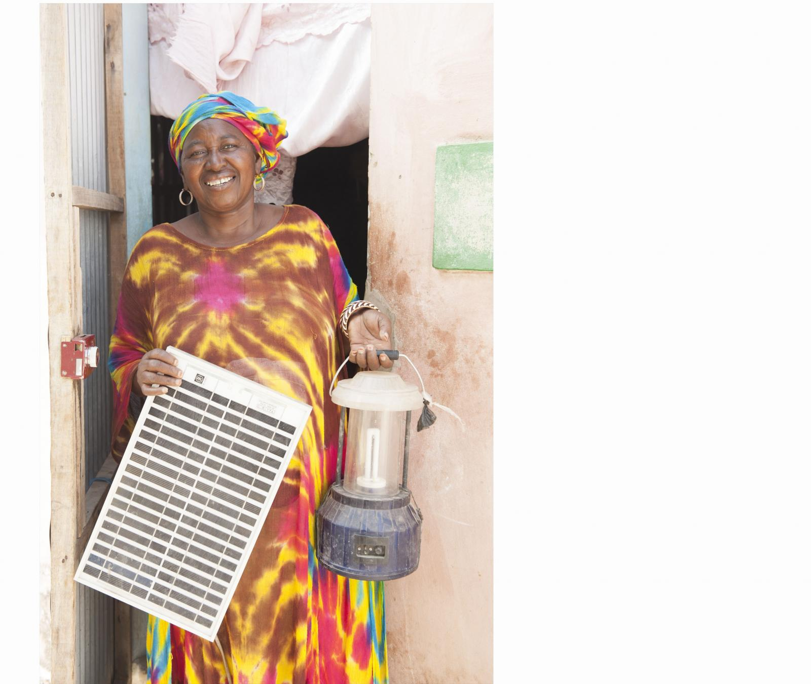 Grandma holds a solar panel and a lantern.