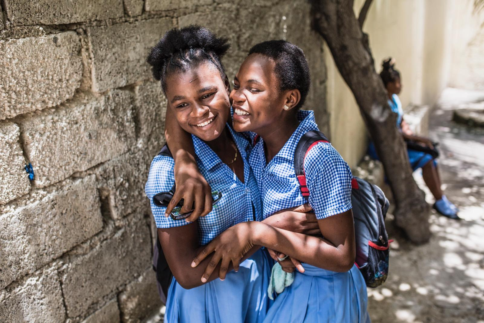 Two school girls hugging each other.