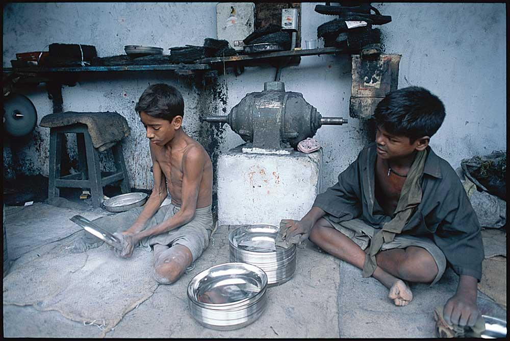 Two boys in India working in mechanics shop