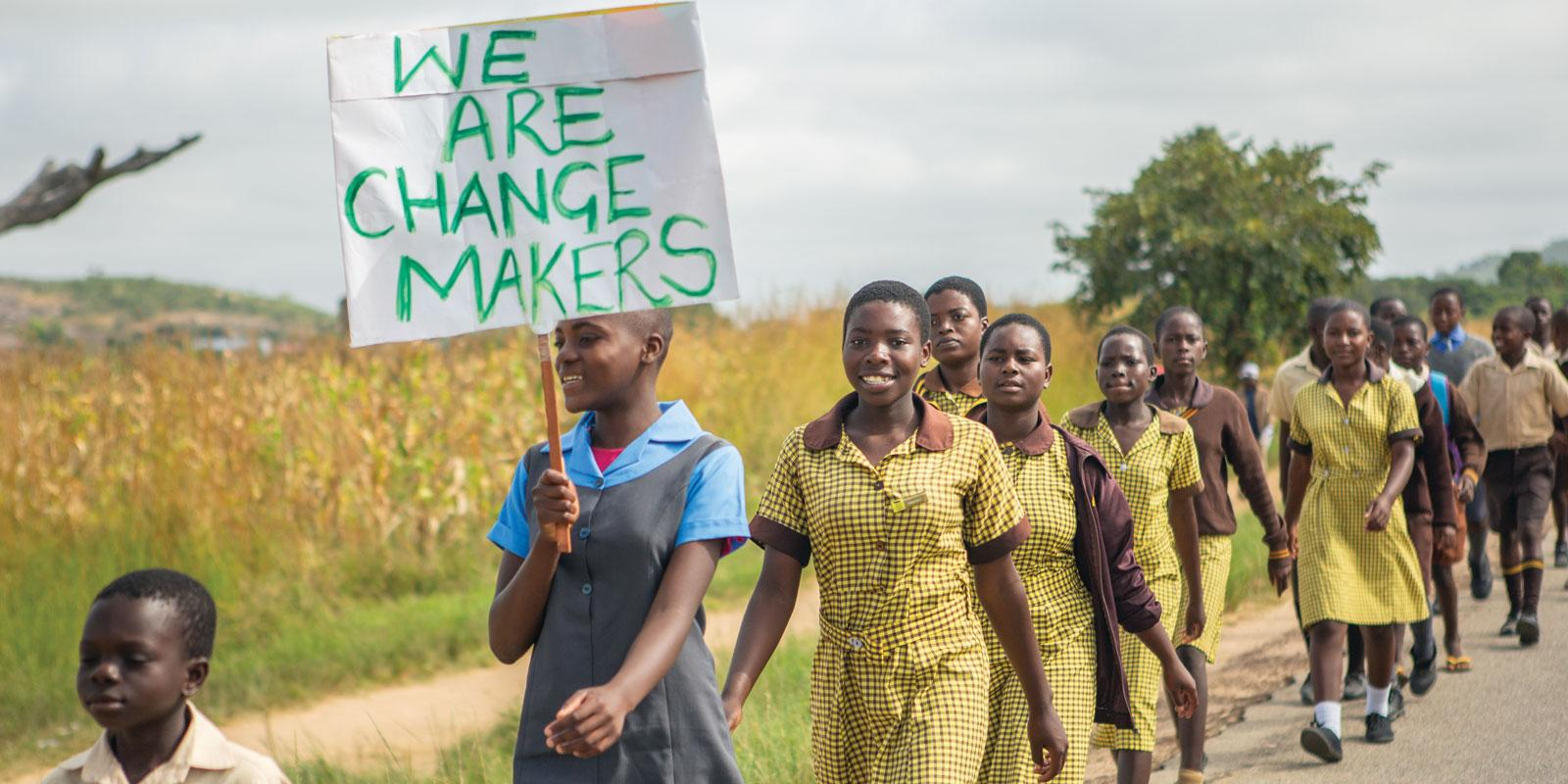 Gils and boys marching on country road with sign: We are changemakers
