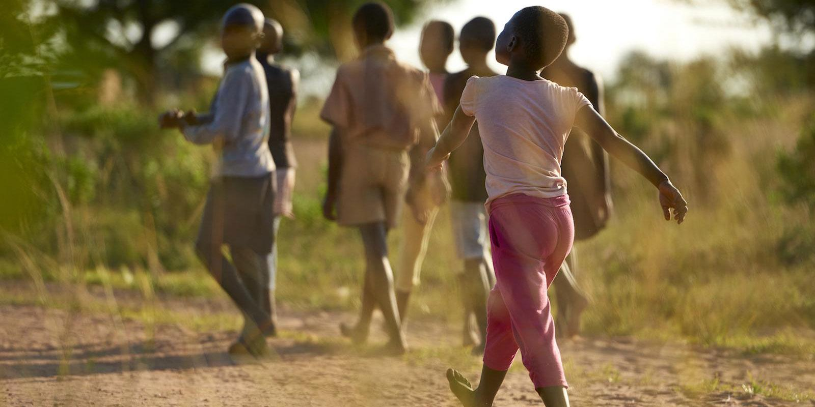 Children walking and running on dusty road