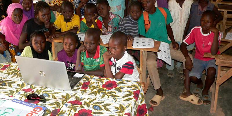 Children watching a computer screen in run -down classroom