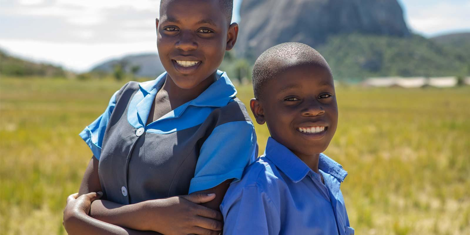 Kim and Hassan, girl and boy, 13, face the camera, wearing their school uniforms.