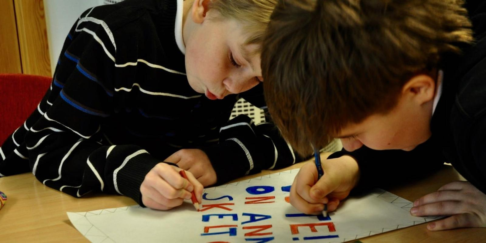 Two boys creating an election poster