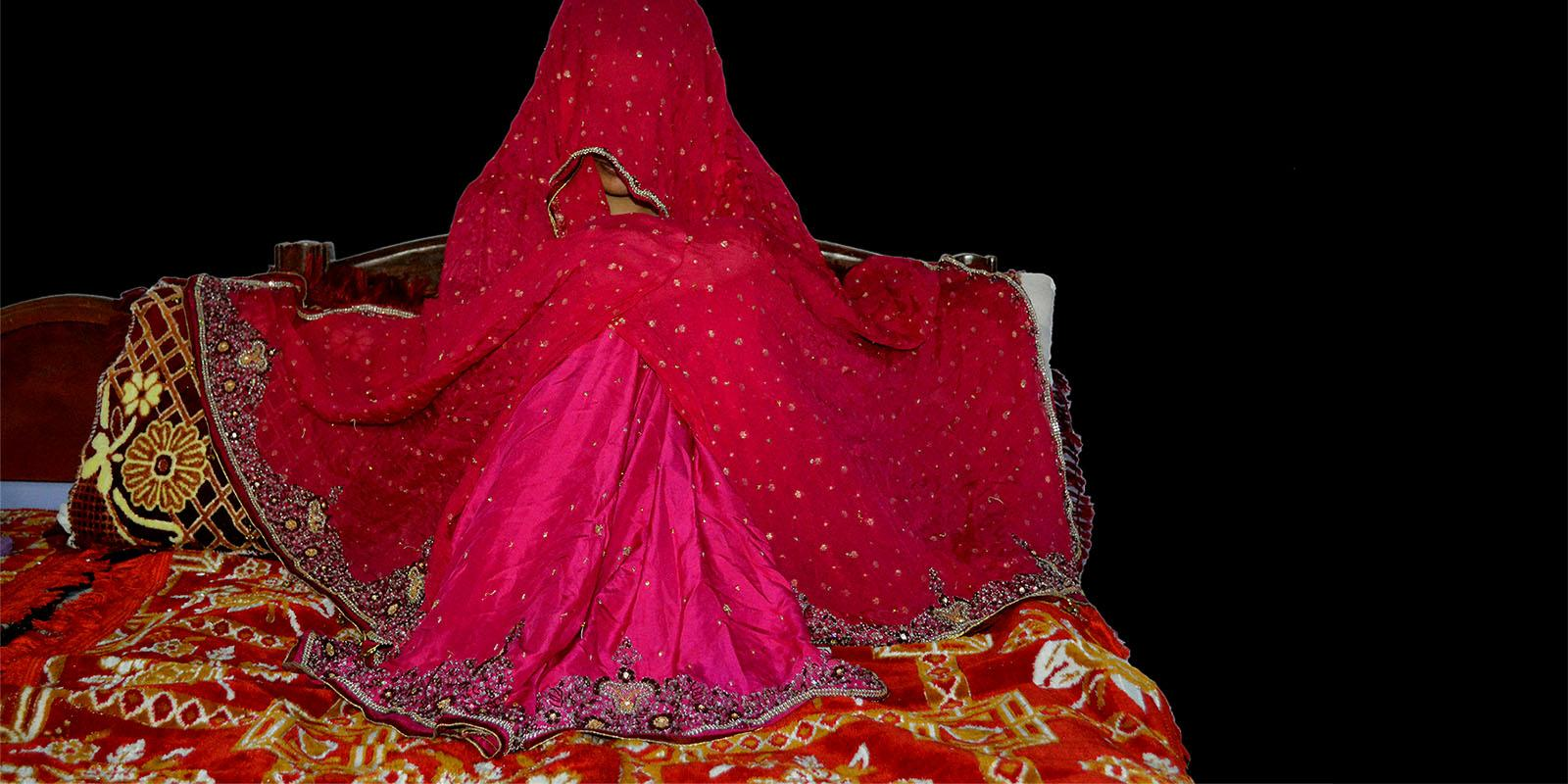 A girl sits covered on the floor, waiting to be married