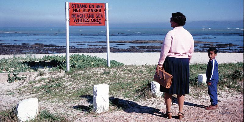 Black lady and child standing on the beach in front of apartheid sign