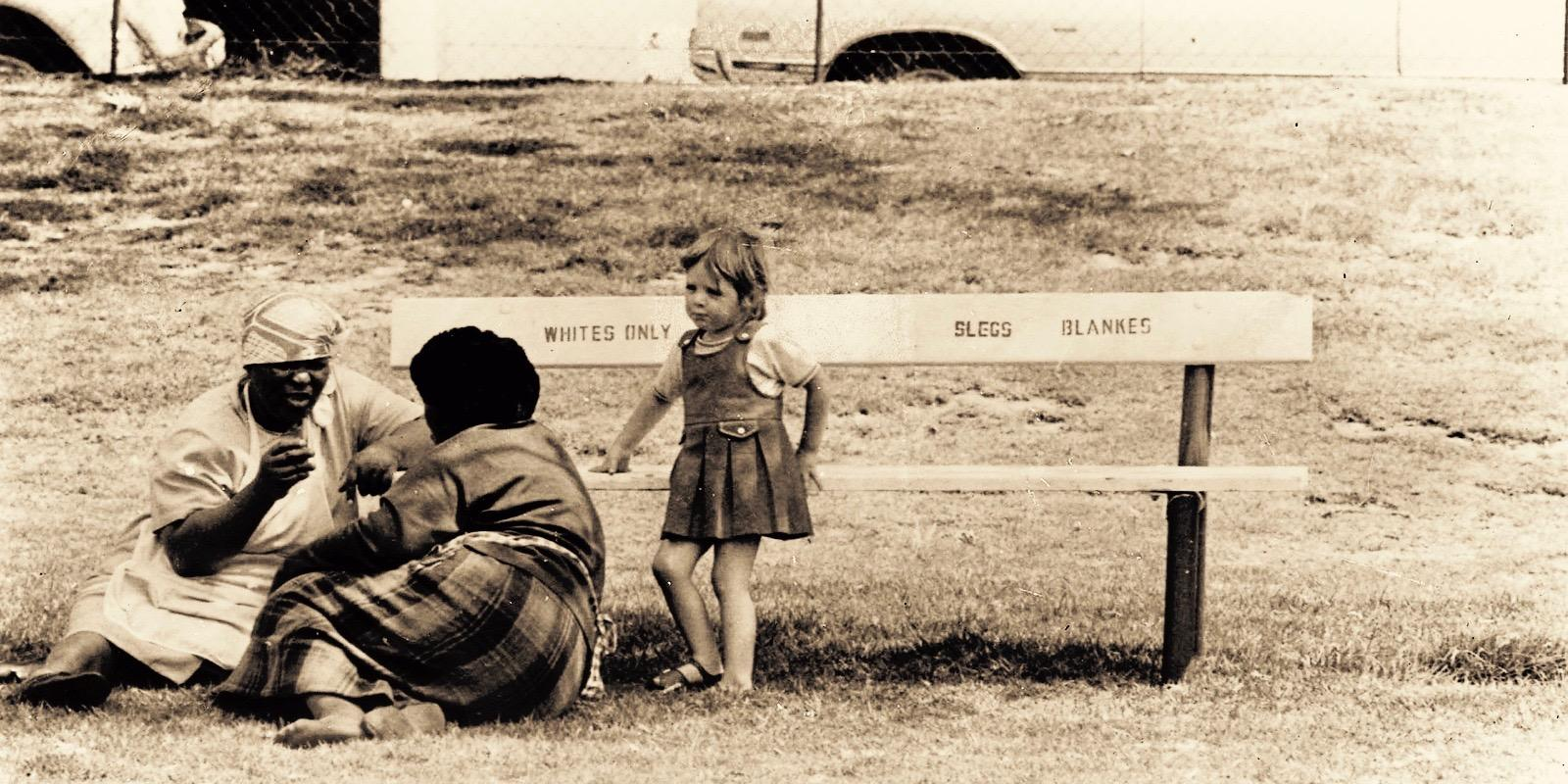 white girl child near a bench for whites only, with two black women sitting on the grass