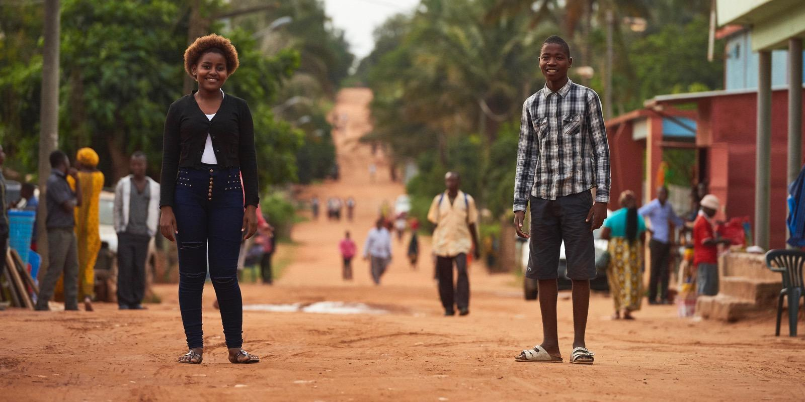 Girl and boy standing in dirt road