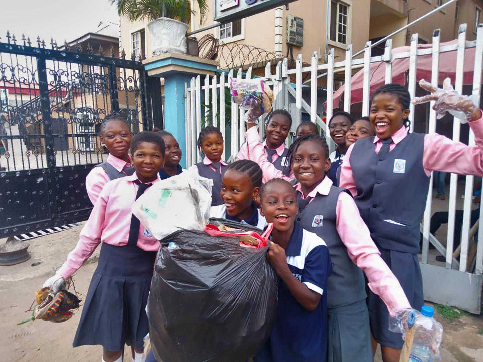 A group of girls smiling, looking into the camera, while holding a big plastic bag of litter