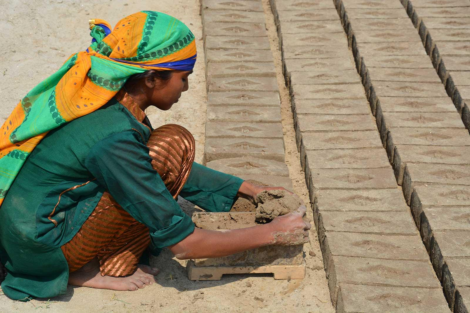 Nisha making bricks under bright sunlight