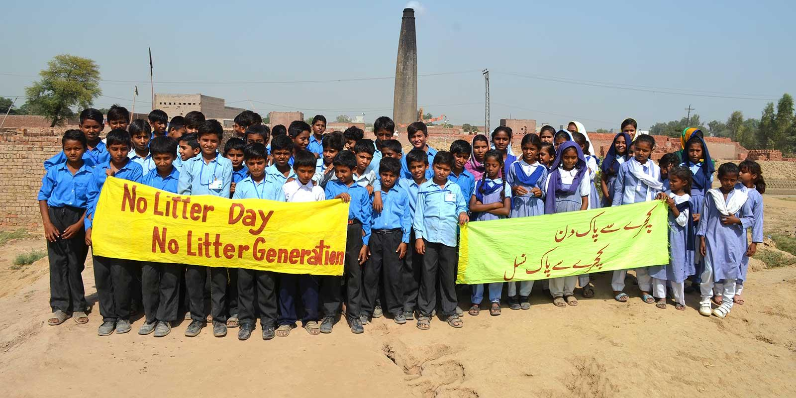 Children standing with signs saying No Litter Generation