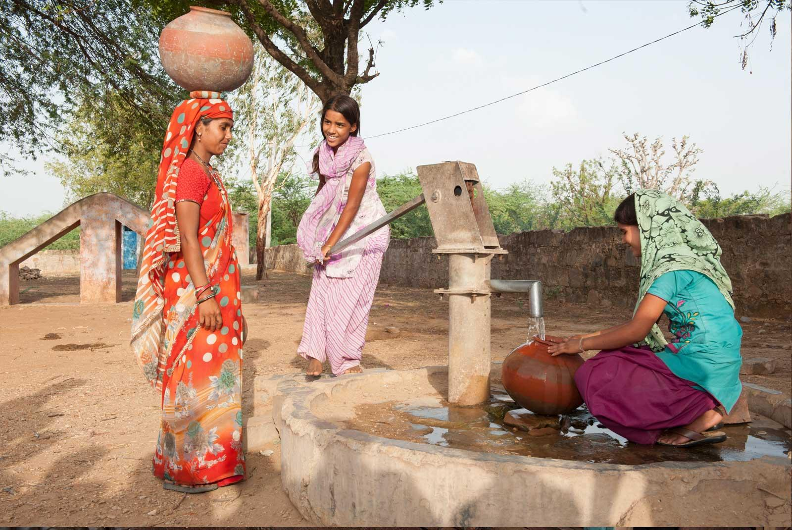 Three girls getting water from pump in India