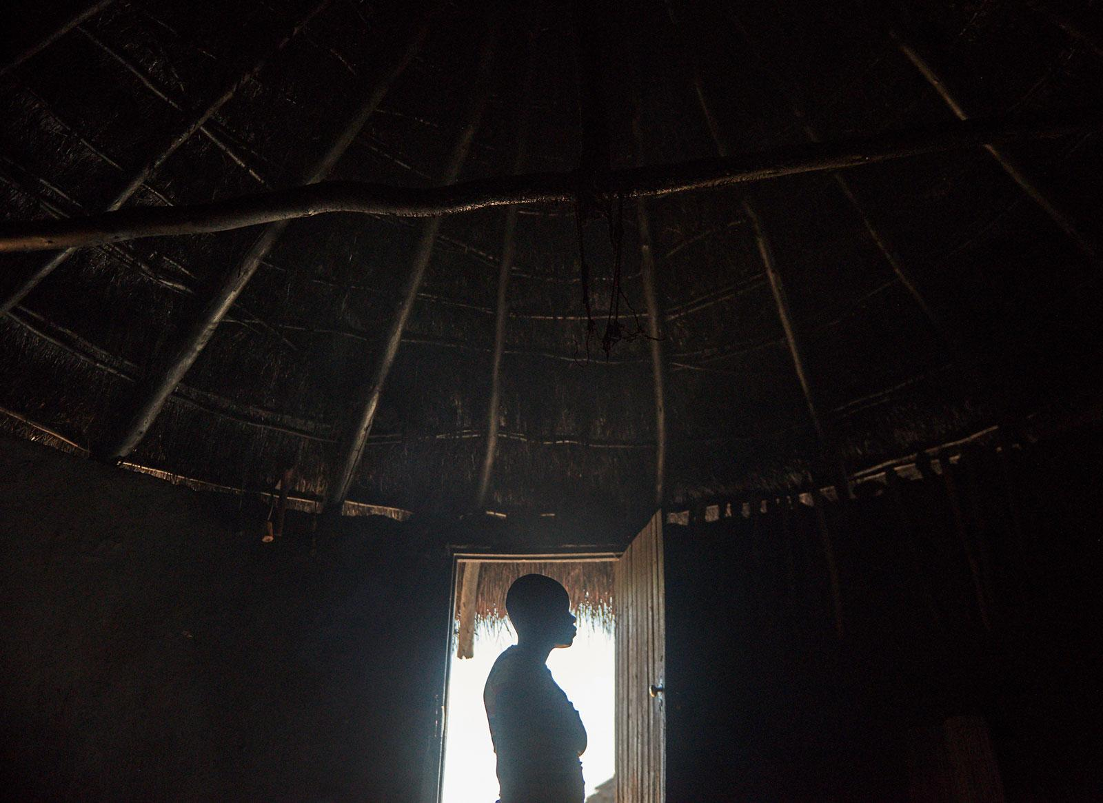 a girl standing in the doorway. the sun is shining outside so only her silhouette is visible