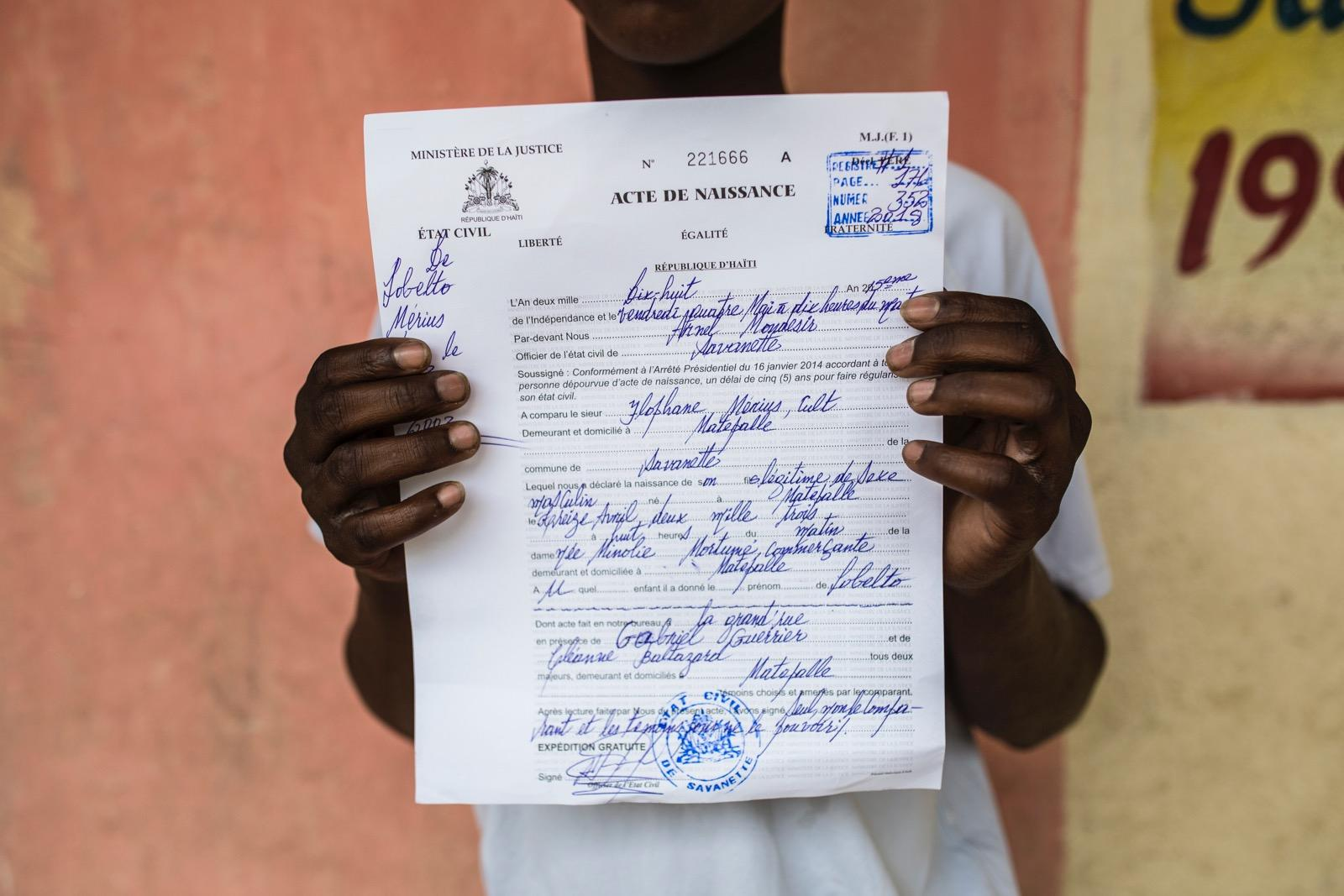 A boy holding up his birth certificate.