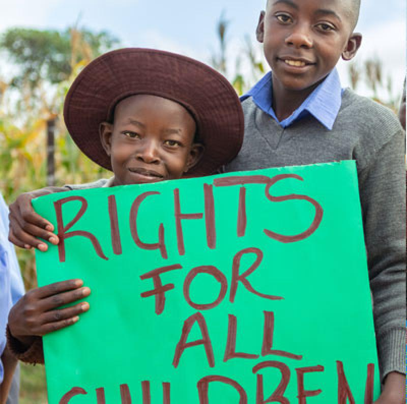Girl and boy with sign: Rights for children