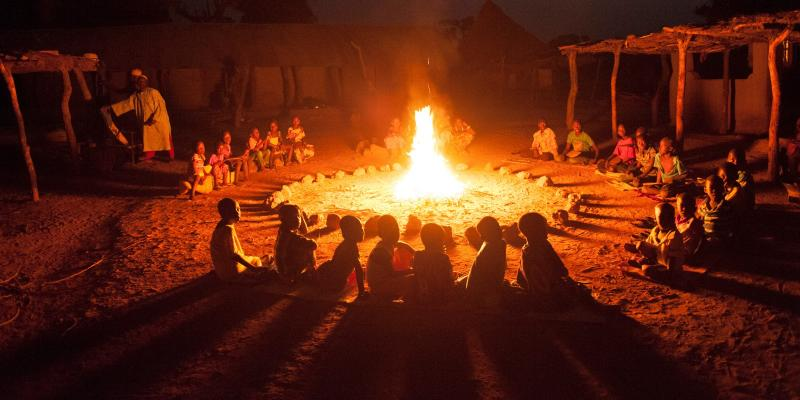 Children sitting around a fire