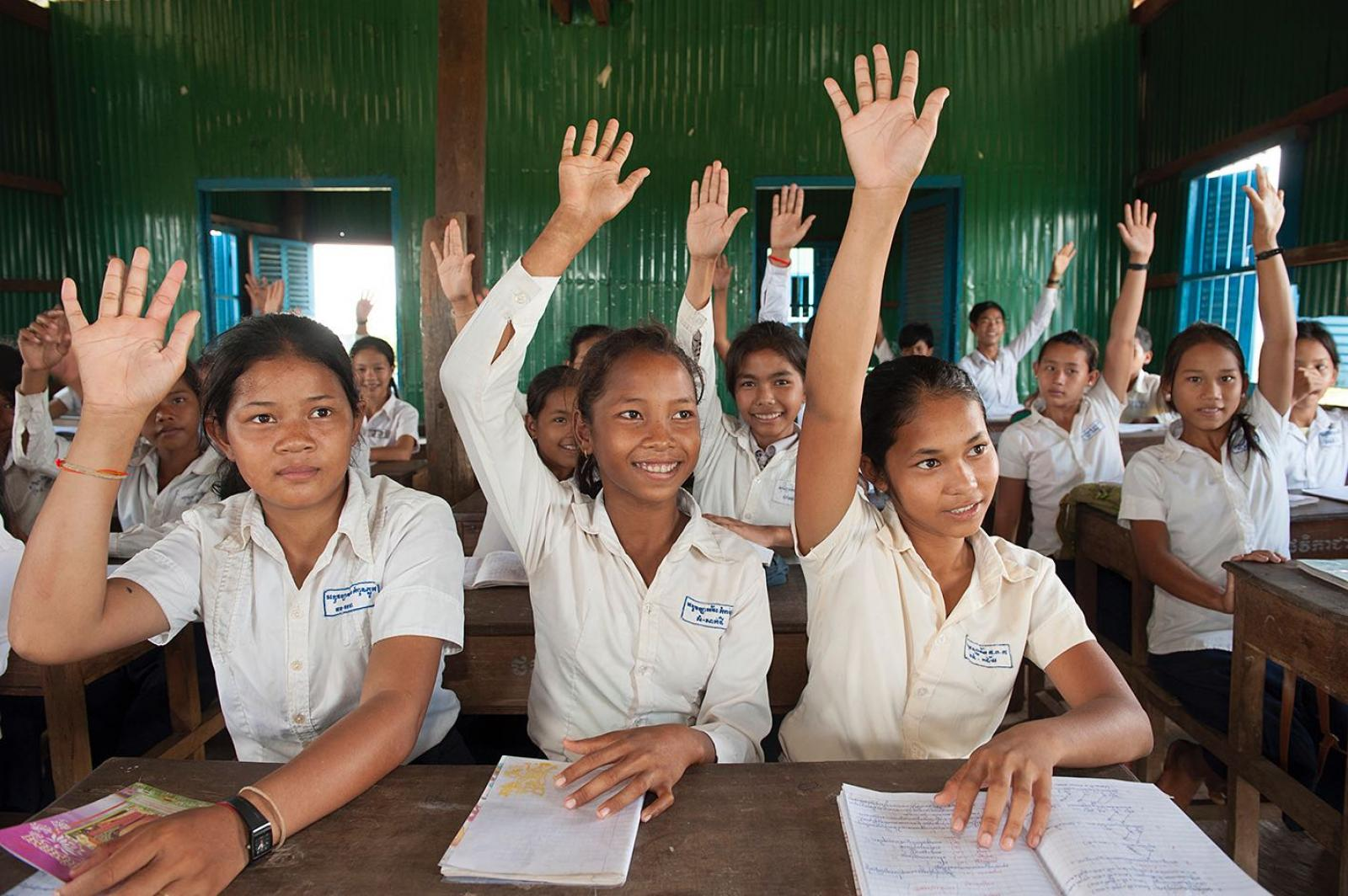Three girls raising hands in classroom