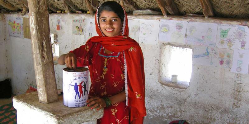 Girl putting vote in ballot box made of can