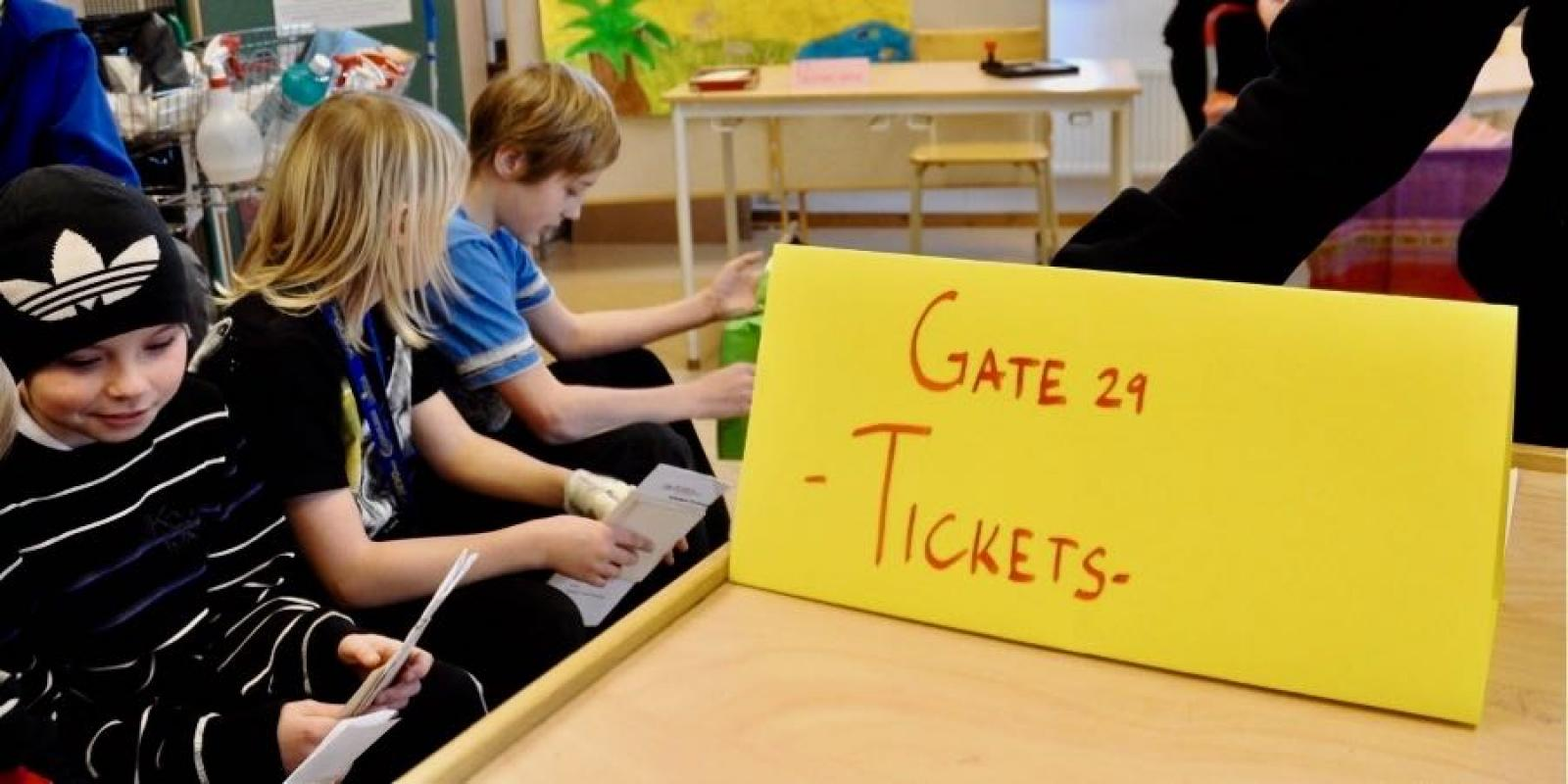 Sign marking an airport gate in a classroom