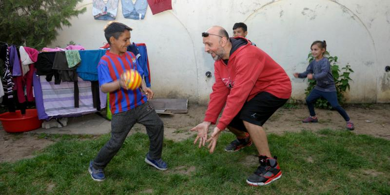 Valeriu playing football with children