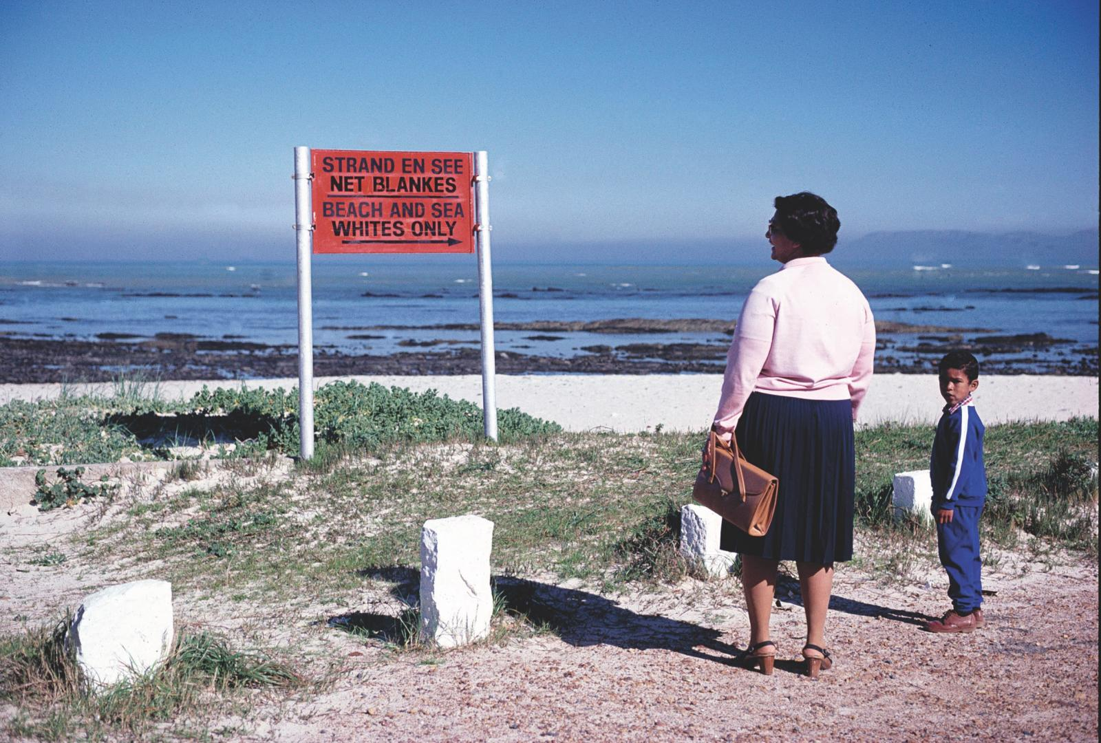 Woman and child looking at sign saying: Whites only