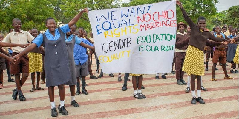 Children holding banner with messages about the rights of the child